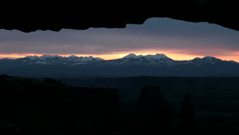 Clouds-of-darkness-lighten-into-delicate-shades-of-pink-as-the-sun-rises-over-Mesa-Arch-in-Canyonlands-National-Park