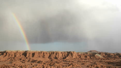 A-rainbow-fades-in-the-sunlight-as-it-arches-over-Goblin-Valley-State-Park