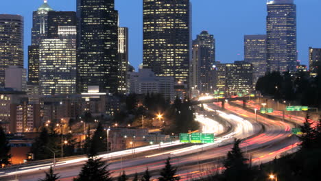As-the-goldenhour-darkens-into-night-accelerated-traffic-blurs-into-streaks-of-light-before-an-illuminated-Seattle-skyline