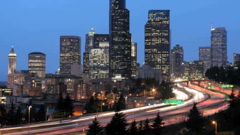 As-the-goldenhour-darkens-into-night-accelerated-traffic-blurs-into-streaks-of-light-before-an-illuminated-Seattle-skyline-1