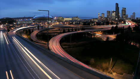 As-the-goldenhour-darkens-into-night-accelerated-traffic-on-the-Seattle-freeway-blurs-into-streaks-of-light-before-an-illuminated-city-skyline
