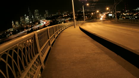 Pedestrians-and-traffic-cross-a-bridge-in-Seattle-at-night