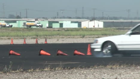 A-White-Car-Squeals-Its-Tires-And-Spins-Out-As-It-Is-Guided-Through-A-Drifting-Course-In-At-Camarillo-Airport-In-Camarillo-California