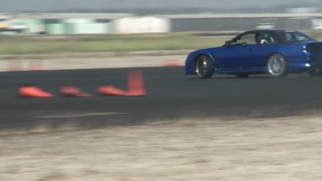 A-Blue-Car-Squeals-Its-Tires-As-It-Is-Skillfully-Guided-Through-A-Drifting-Course-In-At-Camarillo-Airport-In-Camarillo-California