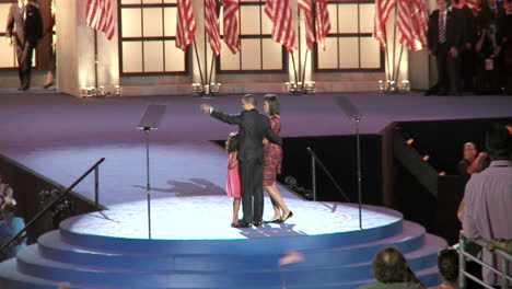 Presidential-Nominee-Barack-Obama-Greets-His-Vice-Presidential-Pick-Joe-Biden-With-Their-Family-S-And-Wave-To-A-Packed-Investco-Field-At-The-End-Of-The-2008-Democratic-National-Convention-In-Denver-Colorado-People-Clap-And-Cheer
