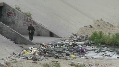 A-Man-Walks-Amongst-Garbage-And-Litter-In-A-Drainage-Ditch