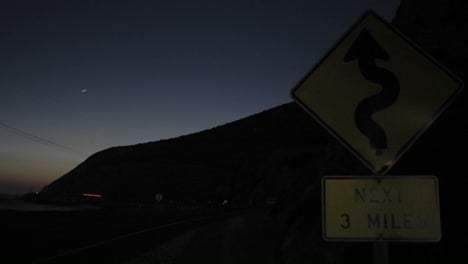 A-Time-Lapse-Shot-Of-Traffic-At-Night-Passing-A-Roadsign