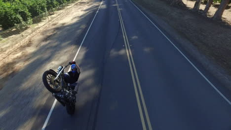 Aerial-Over-A-Motorcycle-Stuntman-Doing-An-Outrageous-Wheelie-On-A-California-Road