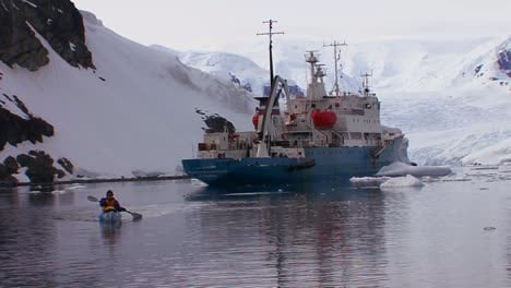 A-man-kayaks-near-a-ocean-research-vessel-in-Antarctica