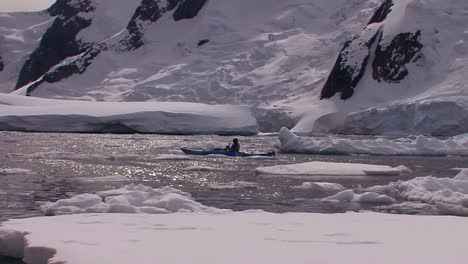 A-man-paddles-a-kayak-through-the-Arctic-or-Antarctica-region-near-vast-ice-fields-and-glaciers
