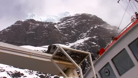 Low-angle-of-an-oceanic-research-vessel-passing-below-high-cliffs-in-Antarctica