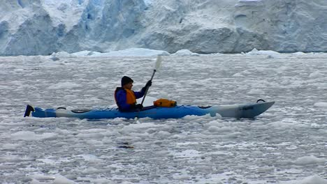 A-man-paddles-a-kayak-in-the-Arctic-or-Antarctic-with-many-icebergs-nearby