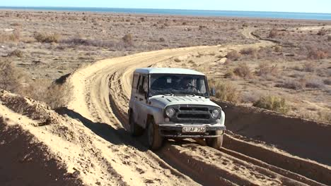 An-old-jeep-passes-on-a-deeply-rutted-road-near-the-Aral-Sea-in-Kazakhstan-or-Uzbekistan