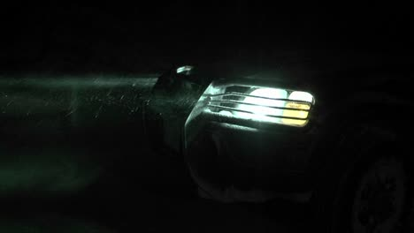 Close-up-of-a-car-headlight-shining-through-a-snowfall-at-night