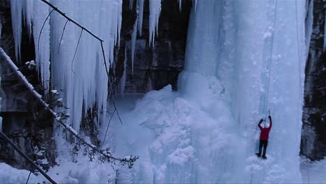 A-man-ice-climbs-a-frozen-waterfall