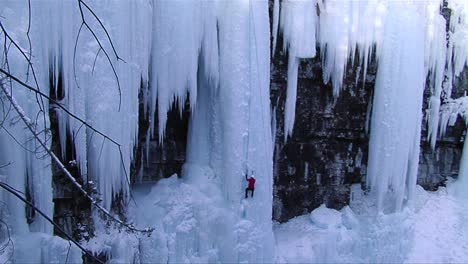 Wide-shot-of-a-man-climbing-a-frozen-waterfall