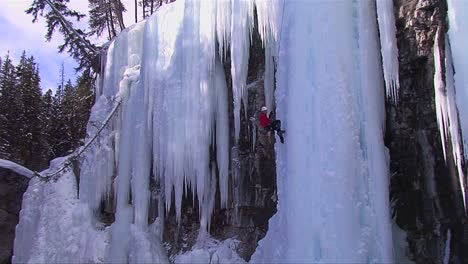 An-extreme-wide-shot-of-a-man-climbing-a-frozen-waterfall