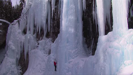 Wide-shot-of-a-man-climbing-up-a-frozen-waterfall