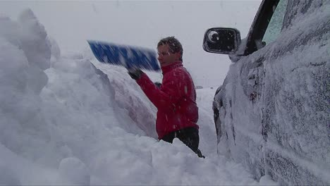 A-man-digs-his-car-out-of-a-snowstorm-in-winter