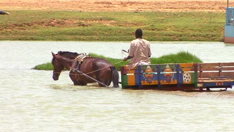 A-man-rides-his-horse-pulling-a-cart-across-a-river-in-Mali-Africa