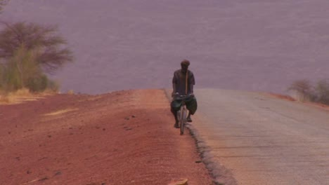 A-man-rides-a-bicycle-on-as-remote-road-across-the-Sahara-desert