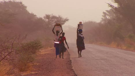 Women-walk-carrying-goods-on-their-heads-through-the-Sahara-desert-in-mali