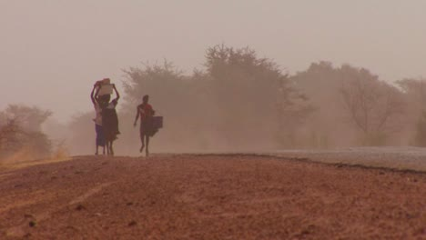 Women-walk-carrying-goods-on-their-heads-through-the-Sahara-desert-in-mali-1