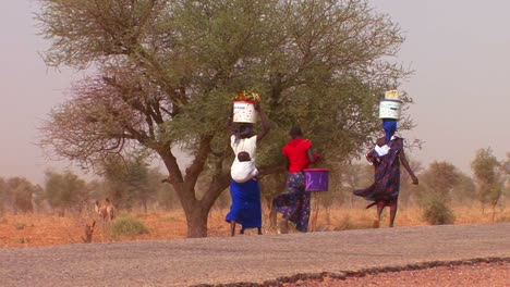 Women-walk-carrying-goods-on-their-heads-through-the-Sahara-desert-in-mali-3