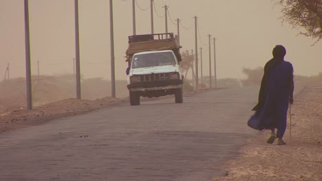 A-Touareg-person-walks-down-a-road-through-the-Sahara-desert-in-Mali-during-a-windstorm