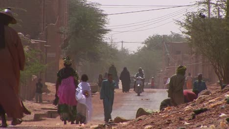 People-walk-down-a-road-through-the-Sahara-desert-in-Mali-during-a-windstorm-1
