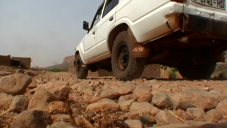 A-UN-type-jeep-drives-down-a-stone-covered-road-in-rural-Mali