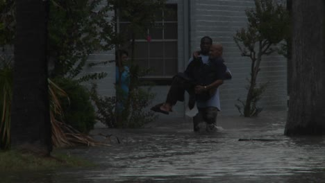 A-man-rescues-a-elderly-citizen-from-flooding-during-a-big-storm