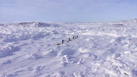 An-Arctic-expedition-moves-across-a-vast-landscape-of-frozen-tundra-on-cross-country-skis-towing-supplies