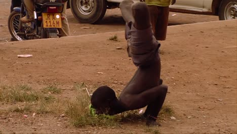 An-African-man-does-a-bizarre-rap-dance-with-his-legs-crossed-in-a-small-village