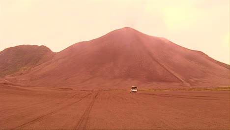 A-vehicle-motors-through-a-desert-landscape-as-a-volcanic-ash-cloud-forms-in-the-background-