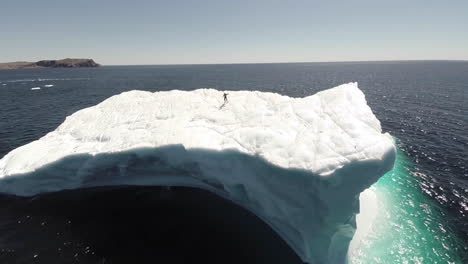 An-amazing-aerial-over-a-man-standing-on-a-huge-iceberg-in-Newfoundland-Canada