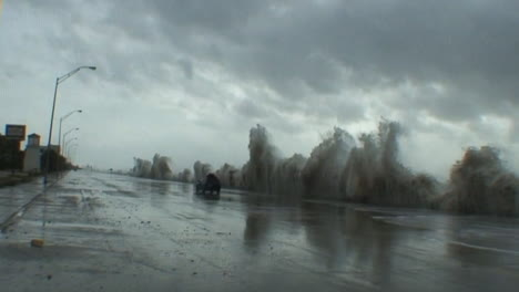 Huge-waves-pound-a-seawall-in-Galveston-Texas-during-a-massive-hurricane-or-storm-as-a-car-drives-by