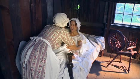 A-19th-century-midwife-assists-a-colonial-era-woman-giving-birth-in-this-reenactment