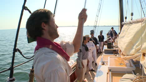 A-man-climbs-the-mast-of-a-19th-century-tall-ship-in-this-historical-reenactment