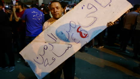 A-man-carries-a-homemade-sign-at-a-large-protest-in-Cairo-Egypt