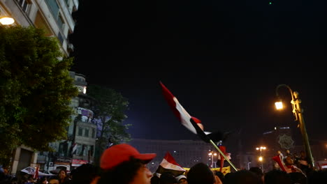 Flags-wave-above-the-crowd-at-a-nighttime-protest-rally-in-Cairo-Egypt