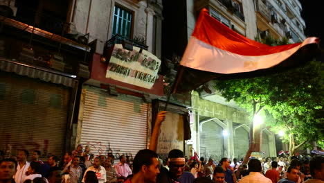 Protestors-wave-flags-at-a-nighttime-rally-in-Cairo-Egypt