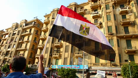 The-sun-shines-through-a-protestor-s-flag-in-Cairo-Egypt
