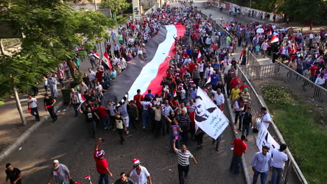Protestors-march-and-carry-a-large-flag-in-Cairo-Egypt