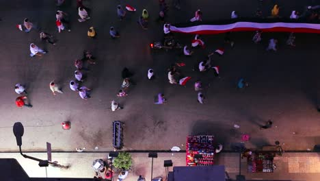 View-from-overhead-looking-straight-down-on-protestors-carry-a-banner-and-march-in-the-streets-of-Cairo-Egypt-at-night