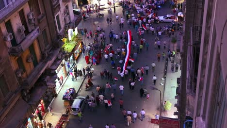 Overhead-view-of-protestors-march-and-carry-banners-in-the-streets-of-Cairo-Egypt-at-night