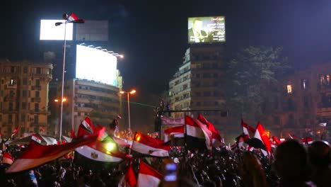 View-from-the-ground-as-protestors-chant-and-wave-flags-at-a-large-nighttime-rally-in-Tahrir-Square-in-Cairo-Egypt