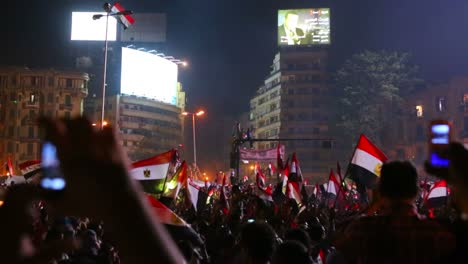 View-from-the-ground-as-protestors-chant-wave-flags-and-take-cell-teléfono-pictures-at-a-large-nighttime-rally-in-Tahrir-Square-in-Cairo-Egypt