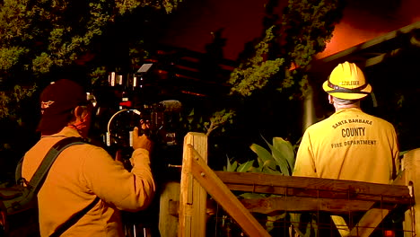 A-News-Crew-Films-As-A-Firefighter-Tries-To-Save-A-Burning-House-During-The-Holiday-Fire-In-Goleta-California
