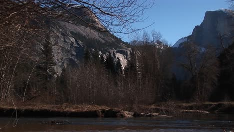 A-Look-At-Bare-Trees-And-Rocks-With-A-Stream-Rushing-Through-The-Foreground